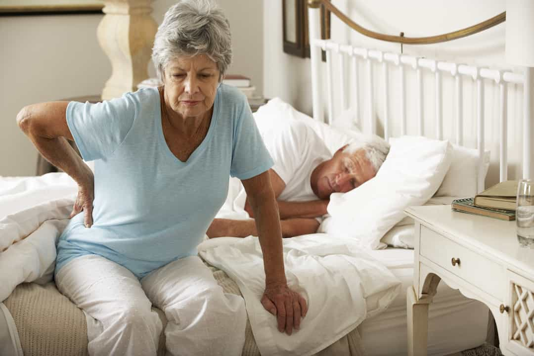 Senior Woman Suffering From Backache Getting Out Of Bed