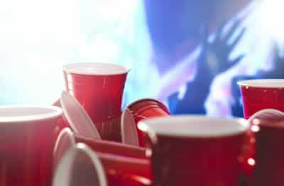 Many red party cups with blurred celebrating people in the background. College alcohol containers in mixed positions.