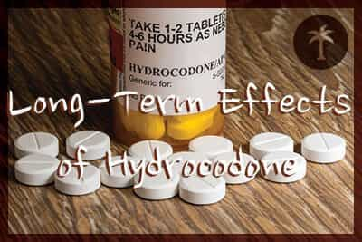 Close photo of prescription bottle for Hydrocodone tablets and pills on wooden table