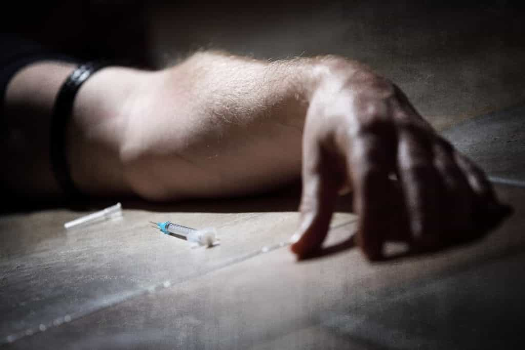 Drug-addict-with-syringe-lying-64002394